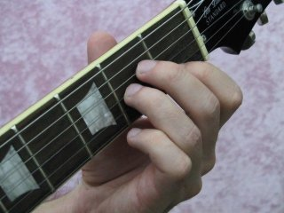 The fretting Hand pressing down the A minor chord