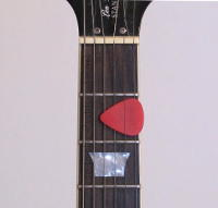 A photo of a guitar pick that is being kept between the strings