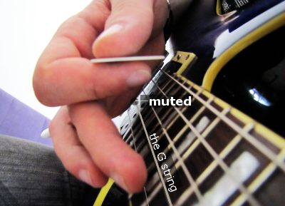 The image illustrates muting the nearby string by putting the side of the picking hand on it